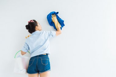 Asian housewife wiping white wall