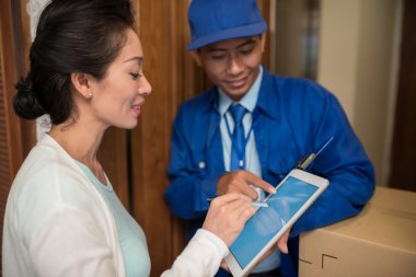 Asian woman signing for parcel