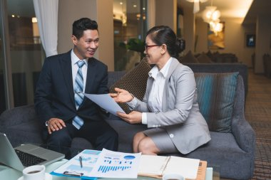 Businessman and businesswoman discussing documents