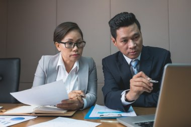 business couple reading information on laptop
