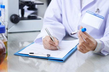 Medical worker writing results of blood test