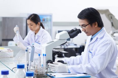 researcher working with modern microscope