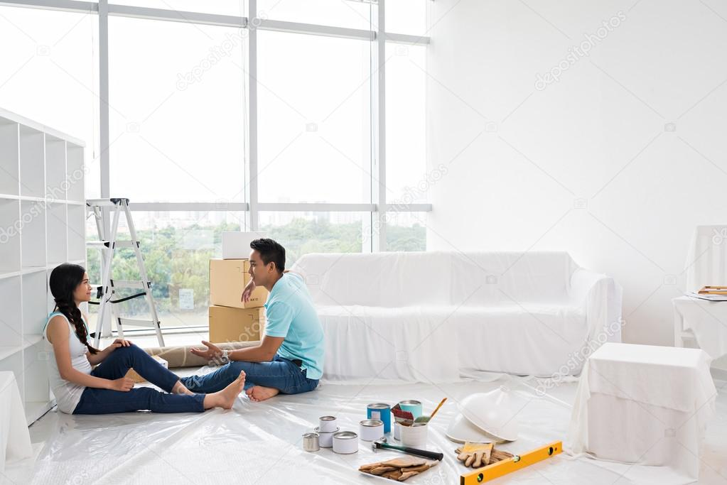 Asian couple making repairs in apartment