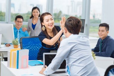 Lady giving high five to colleague