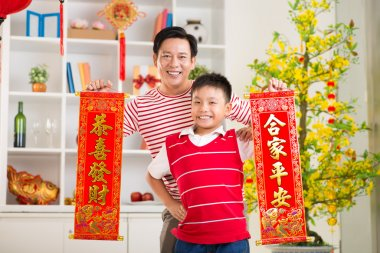 Wishing prosperity. Asian father and son holding banners with wishes for the New Year stock vector