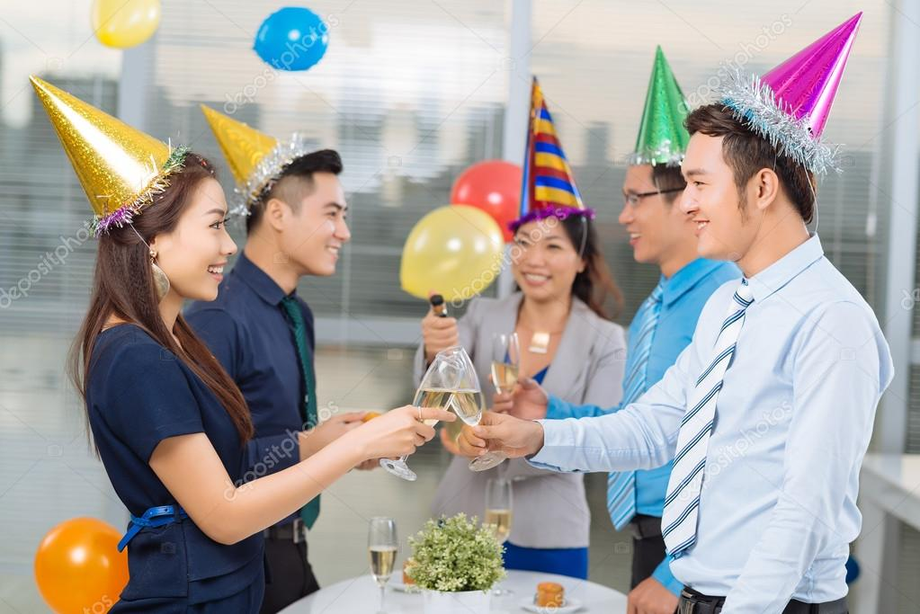 Coworkers clinking glasses at office party stock photo for Fiesta en la oficina