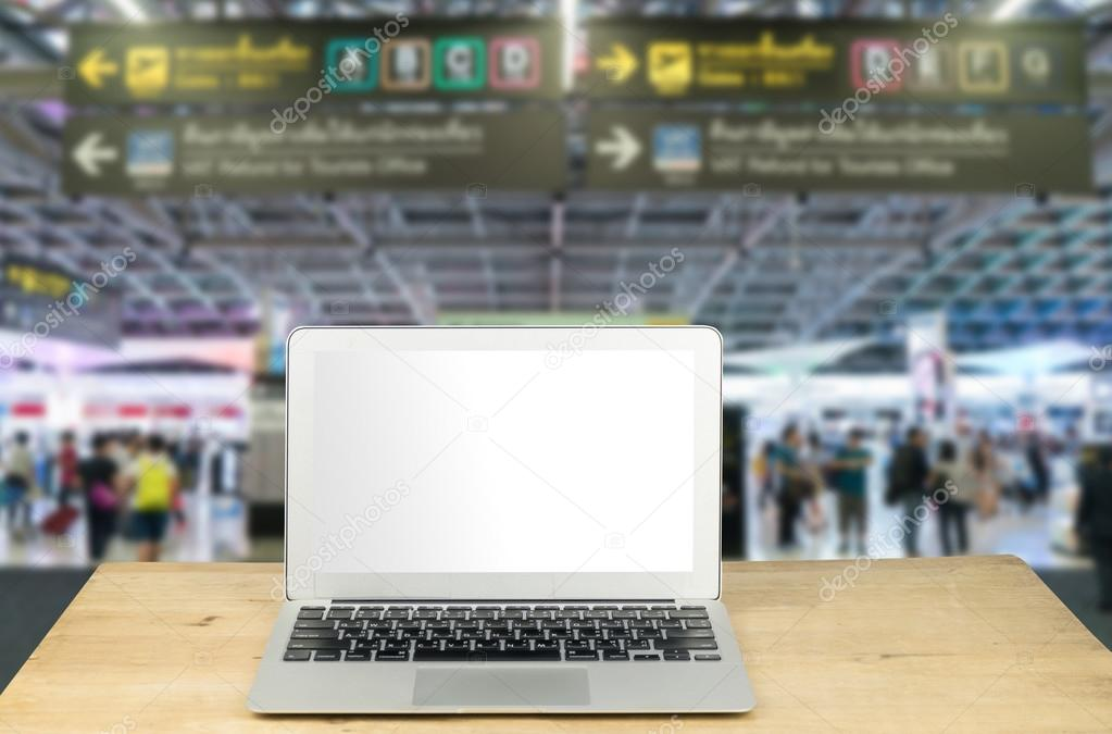 laptop on wood table with blur airport background