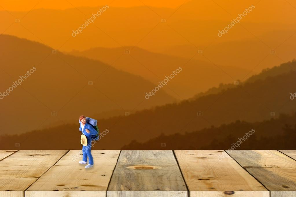 backpacker miniature figure on wood table with nature scene