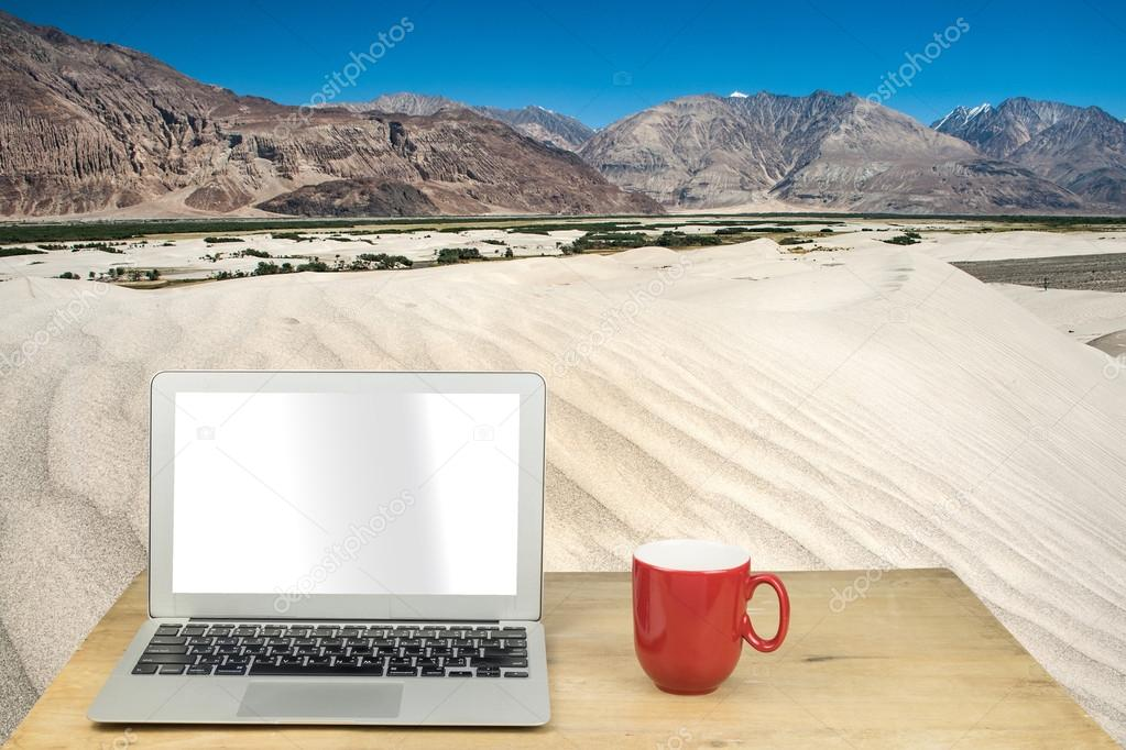 laptop and red mug on wood table with desert in  india