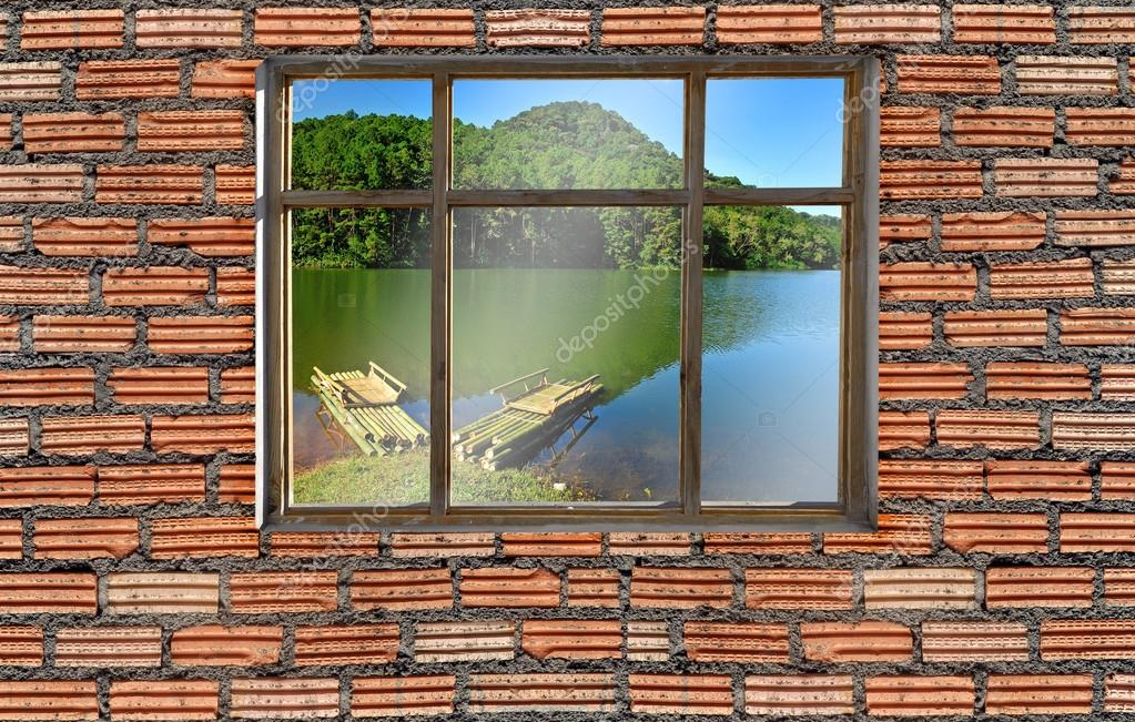 window on brick wall with lake