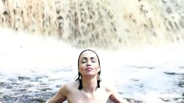 sexy žena se koupe v vodopád v plavkách