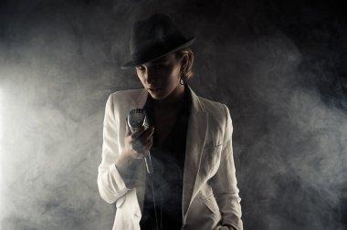 Fashion woman with retro microphone in smoke