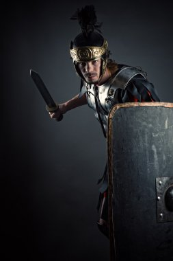 brutal Roman legionary with sword and shield in hands