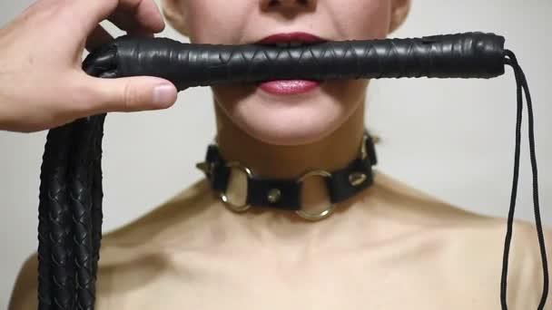 Sklavin attraktive Frau mit Peitsche im Mund