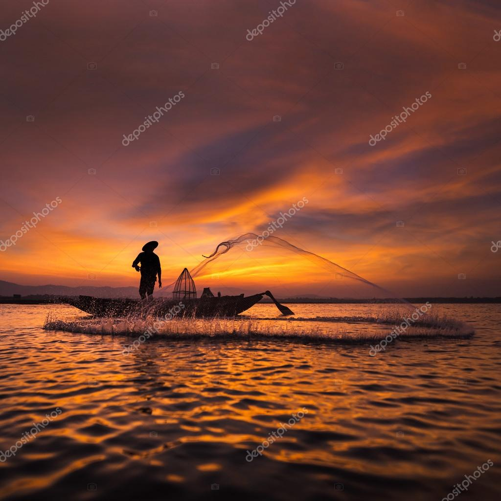 Silhouette of asian fisherman on wooden boat in action throwing a net