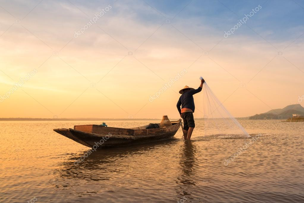 Asian fisherman throwing a net for catching freshwater fish in nature river in the early morning before sunrise