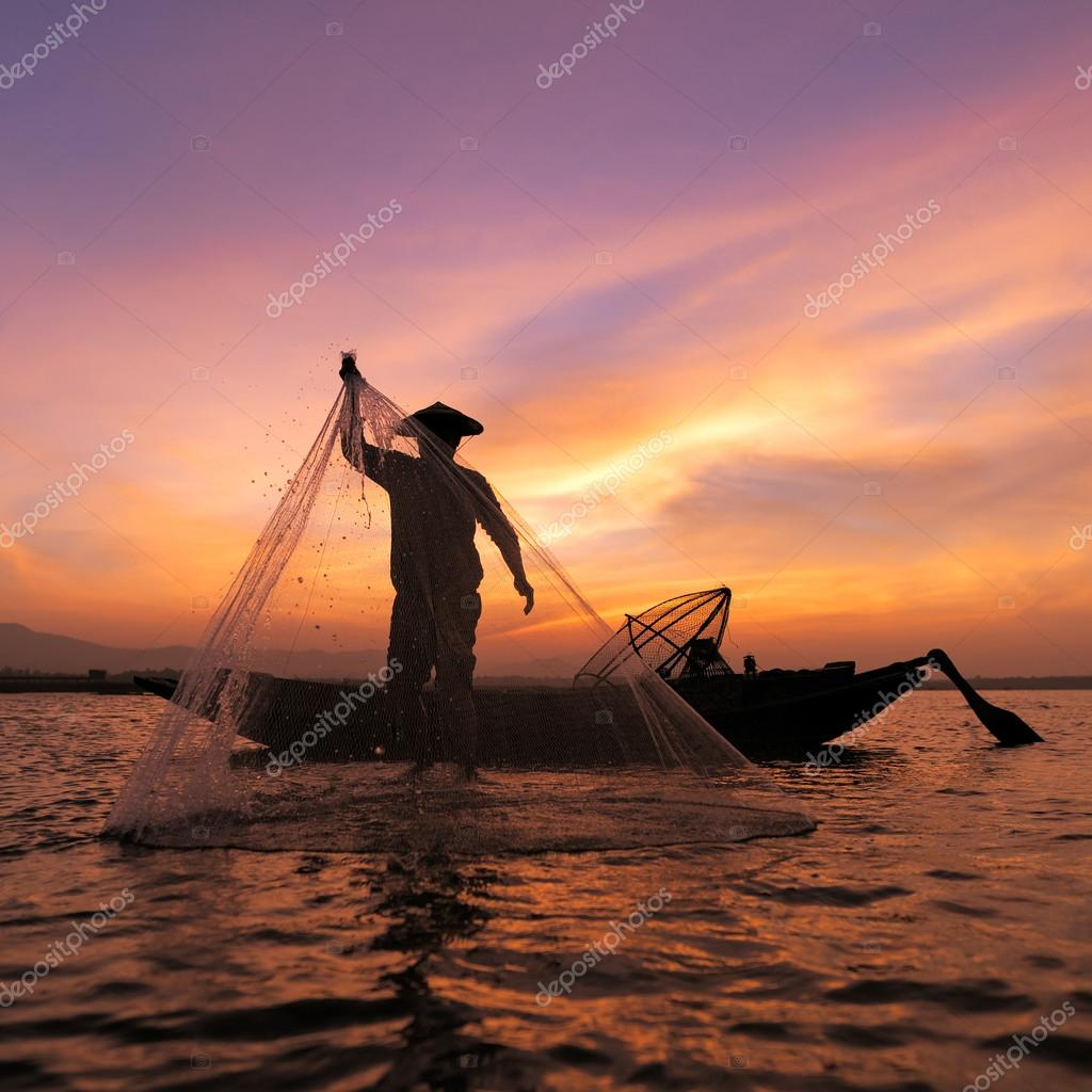 Asian fisherman with wooden boat throwing a net for catching freshwater fish in nature river in the early morning before sunrise