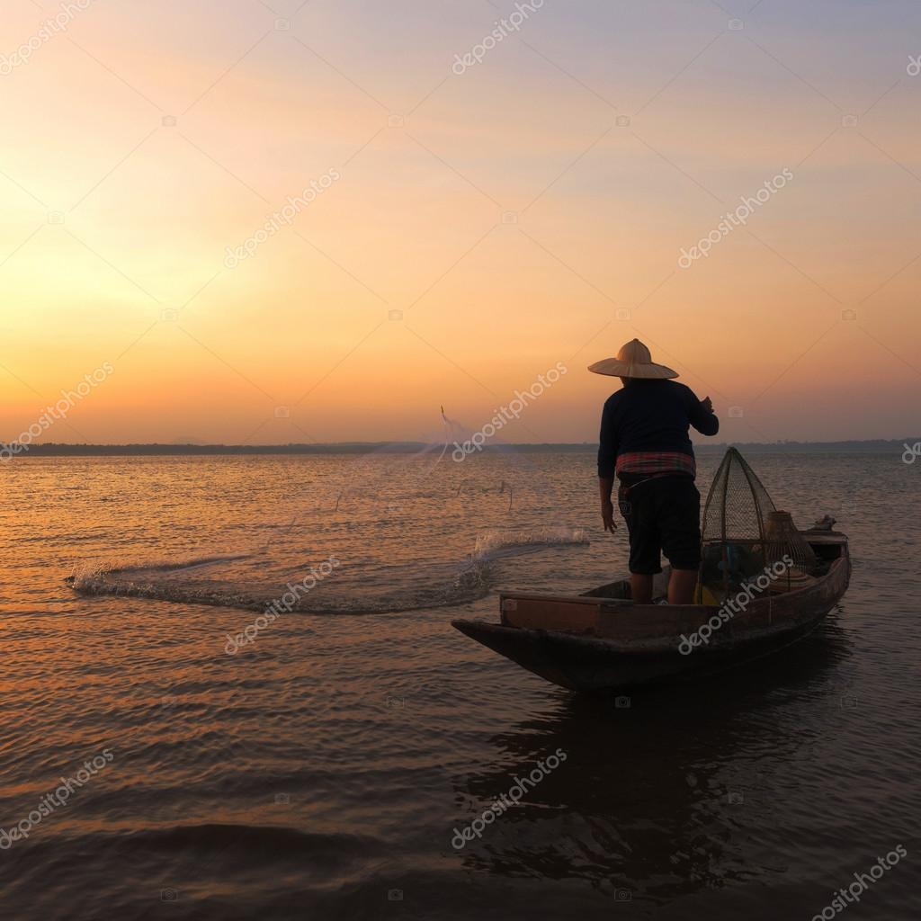 Asian fisherman with his wooden boat going to catching freshwater fish in nature river in the early during sunrise time