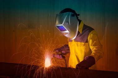 Industrial Worker with safety equipments and protective mask welding steel structure in construction factory.