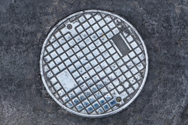 Closeup photo of Old Sewer manhole cover on the urban road