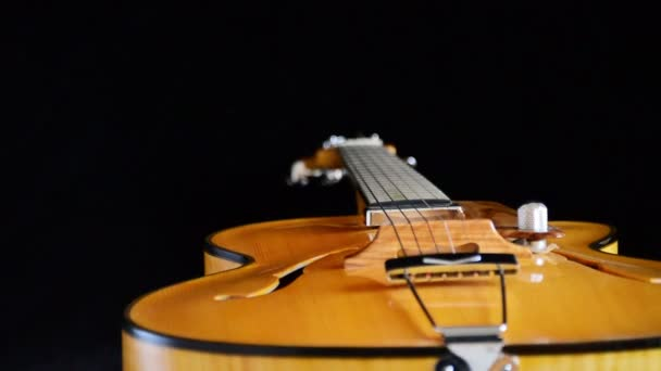 Detail of bridge, strings and efes of a jazz electric guitar gyrating at black background