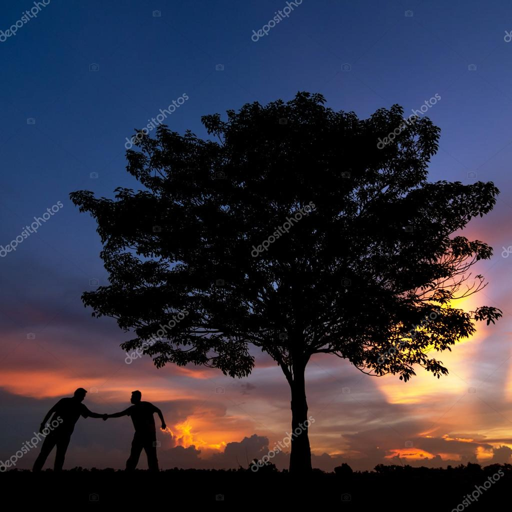 Silhouette of trees and people shake hands