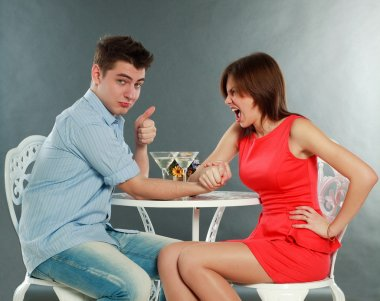 Young aggressive woman winning fighting in arm-wrestling