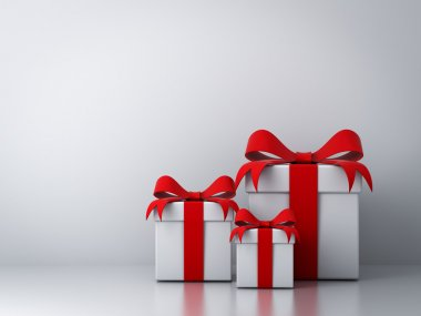 Gift boxes with red ribbon bow and empty white wall