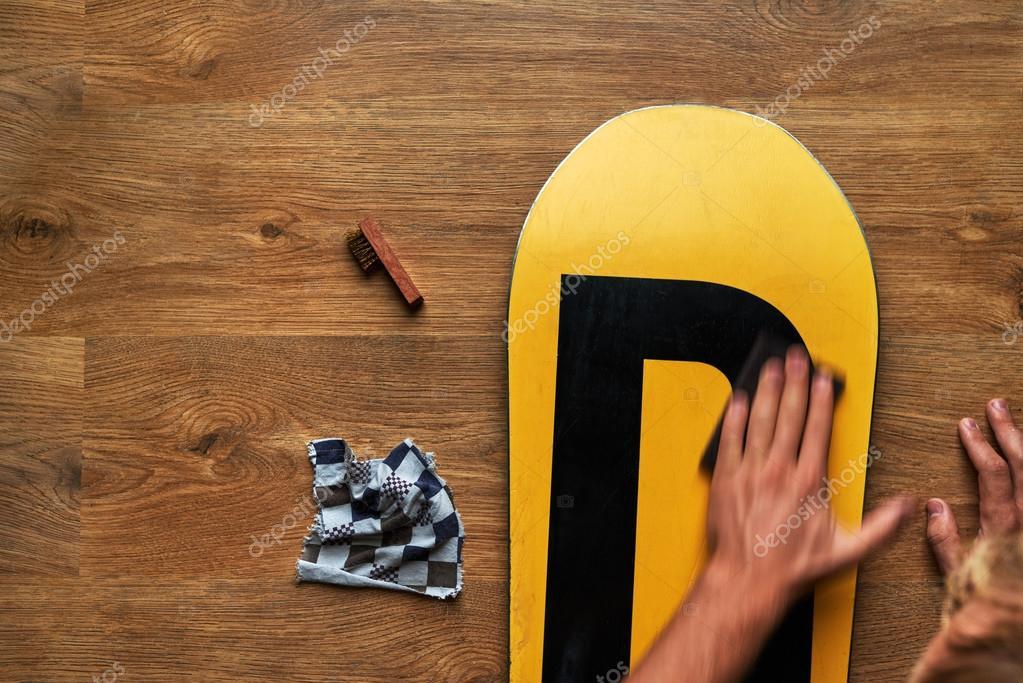 Man wrijft snowboard spons wax op houten vloer u stockfoto