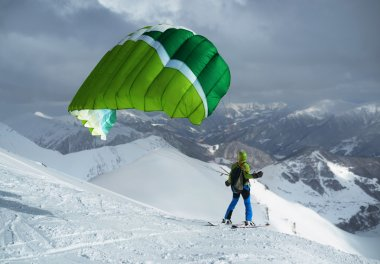green skier starts with a paraglider in  highlands