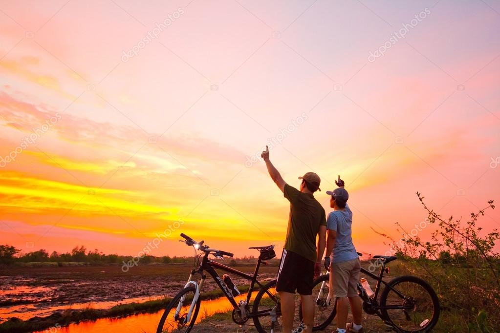 Rear View of a Young Man Standing with a Bicycle at Sunset. Heal