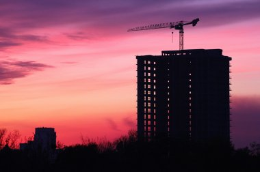 silhouette of building under construction during sunset