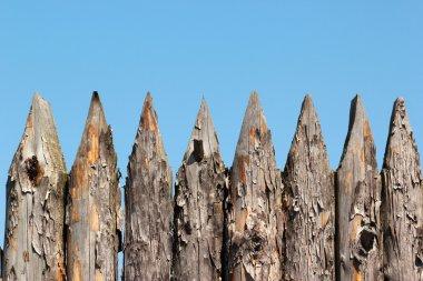 Stockade wooden fence on blue sky background