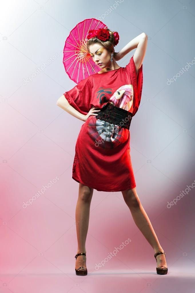 Fashion asian woman wearing traditional japanese red kimono with umbrella,  studio shot. Geisha —