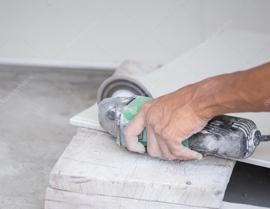 Worker cutting a tile using an angle grinder stock photo worker cutting a tile using an angle grinder stock photo dailygadgetfo Choice Image