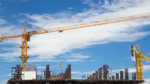 4k Časová prodleva stavebního jeřábu a dělníka stavebnictví s modrou oblohou