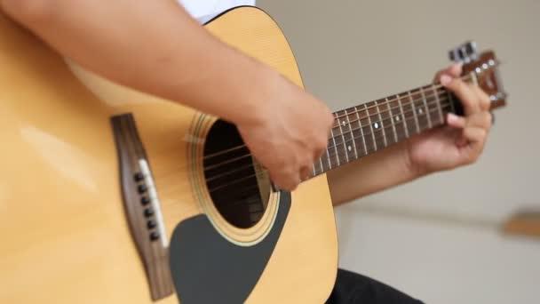Detailní záběr ruky hraje na akustickou kytaru