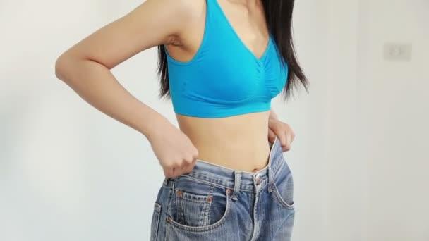 žena ukazuje její hubnutí a nošení její staré džíny