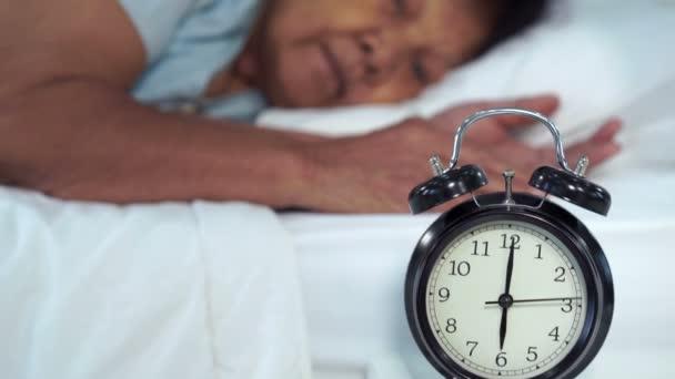 senior žena v posteli stisk tlačítko zdřímnout na časné ranní budík