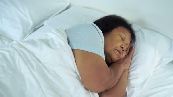 idős nő alszik egy ágyban a hálószobában
