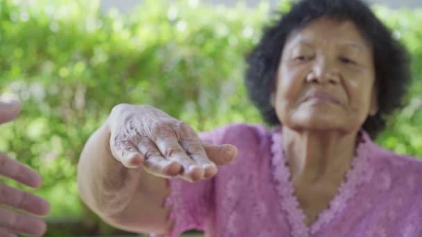 idős nő kéz a kézben fiatal nő