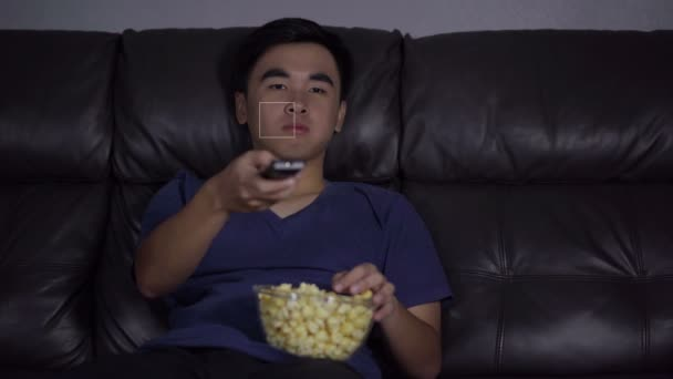 cheerful young man holding remote control and watching TV while sitting on sofa at night