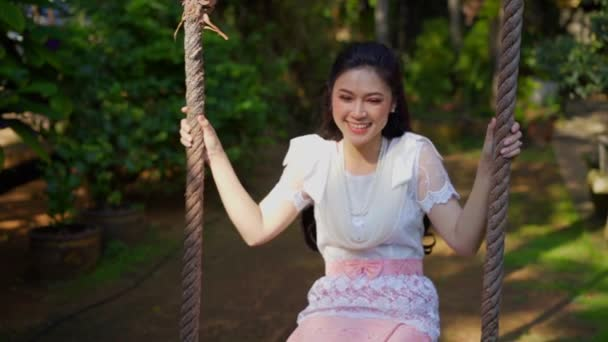 slow-motion of happy young woman in Thai traditional dress relaxing on a wooden swing