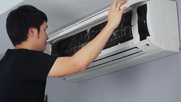 Junger Mann entfernt Luftfilter der Klimaanlage zur Reinigung zu Hause