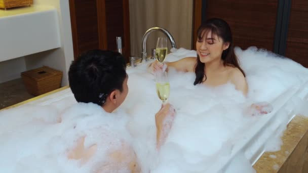 relaxed couple drinking wine from glass while enjoying bubble bath in bathtub