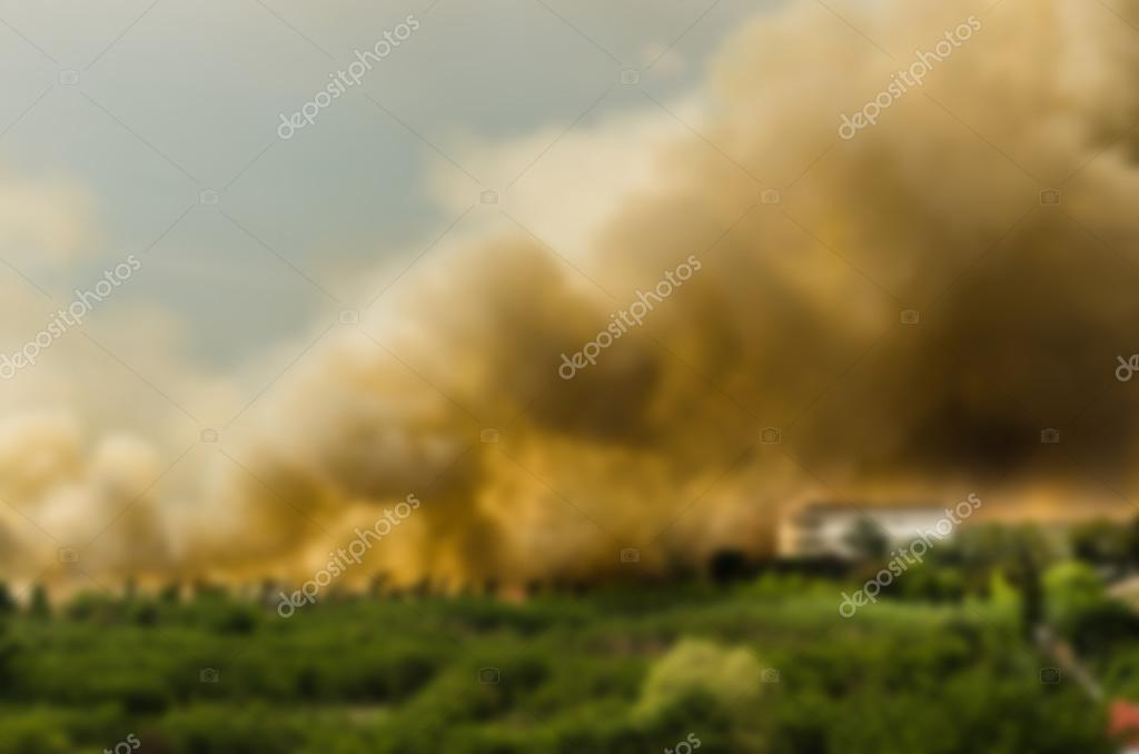Blur effect of Forest fires in the city, causing a large flame and smoke in the air is very hot days. Firemen rush to help prevent the spread of fire to the village