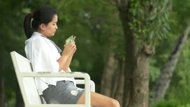 Young asian woman using smartphone and look like relaxing in outdoors looking happy and smiling:Full HD