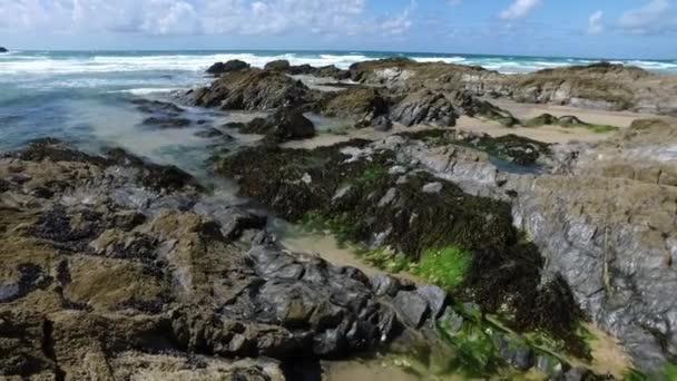 Jemné boční ward pan přes skály a mořských řas, s vzdálené mys a horizont, jako příliv děje Cornish beach