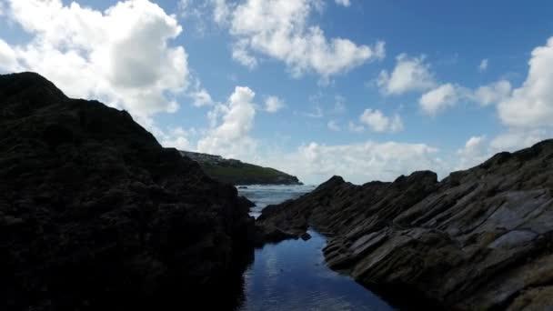 Jemně nahoru pan přes pobřežní devonské rock rockpools odhalit šplouchajícími vlnami přichází příliv a vzdálené mys, v létě, Newquay, Cornwall, Velká Británie