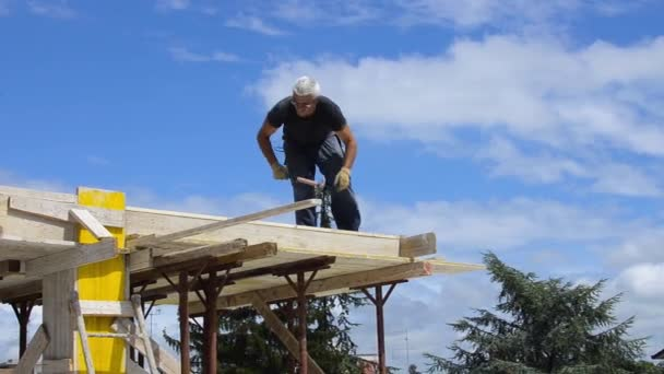 Práce stavební pokrývač přibíjení dřevěné desce s kladivem na střešní instalace